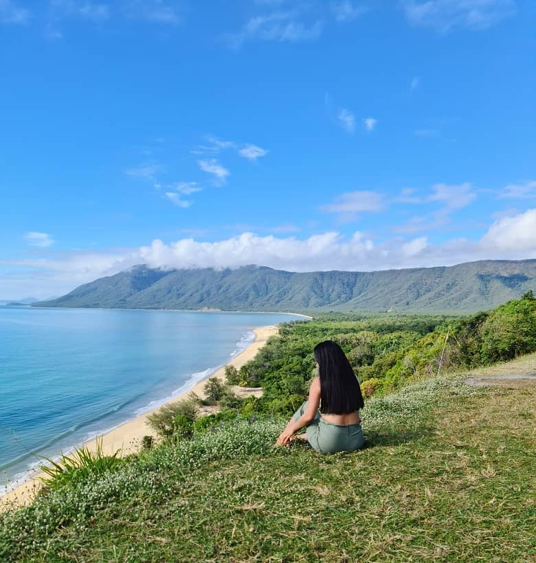 a picture of a woman on the top of the hill, overlooking the coastline