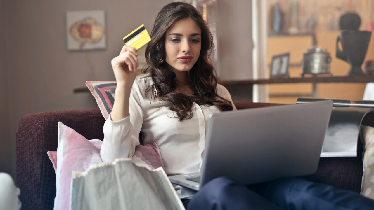 Photo of a woman with brown hair sitting on a brown couch with a silver laptop and gold credit card in hand