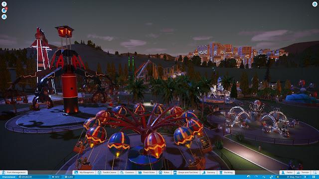 Screenshot of an amusement park at night in Planet Coaster