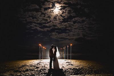 Novios en una playa de noche cerrada iluminados por la luna y antorchas