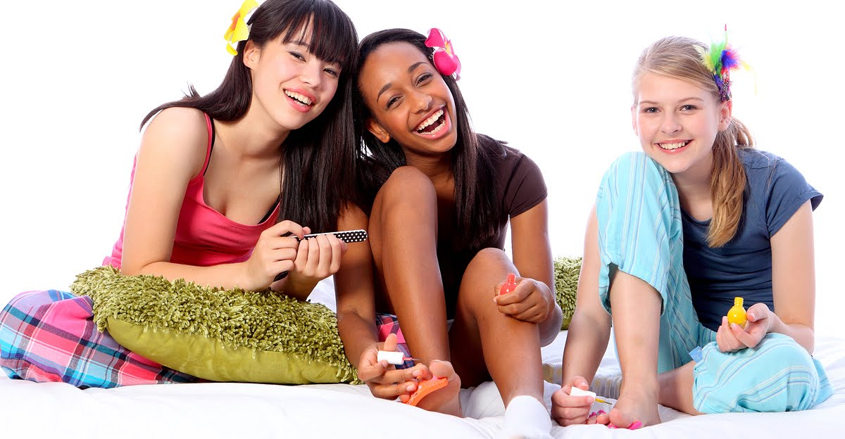 Three teens smiling at a slumber party.