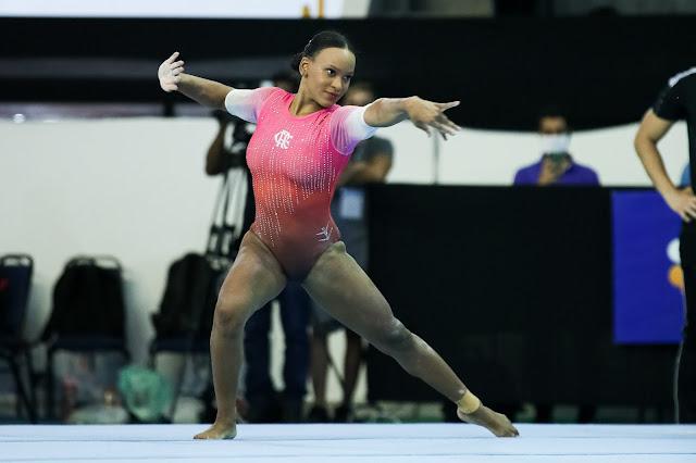 Rebeca Andrade se apresenta no solo. Ela veste um leotard colorido em rosa e vermelho e detalhes em strass