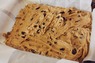 cookie dough spread out evenly in a baking tray lined with baking paper