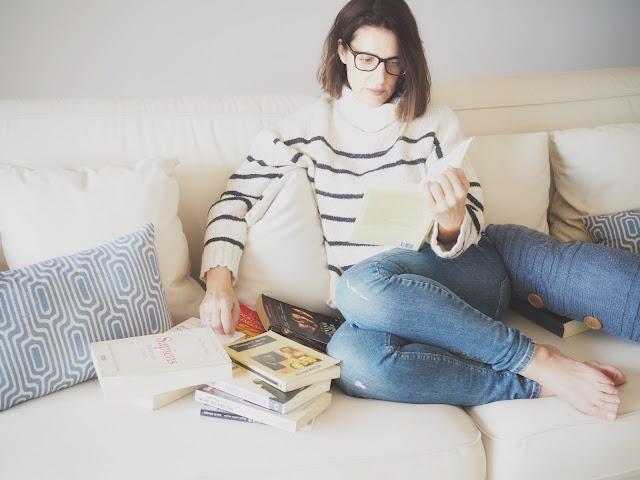 Mujer leyendo en un sofá rodeada de libros