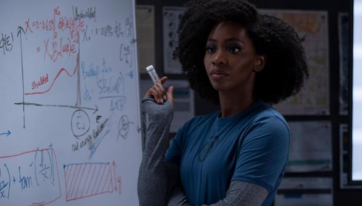Imagem: a personagem Monica Rambeau em uniforme azul da ESPADA, segurando um pincel e ao fundo um quadro branco.