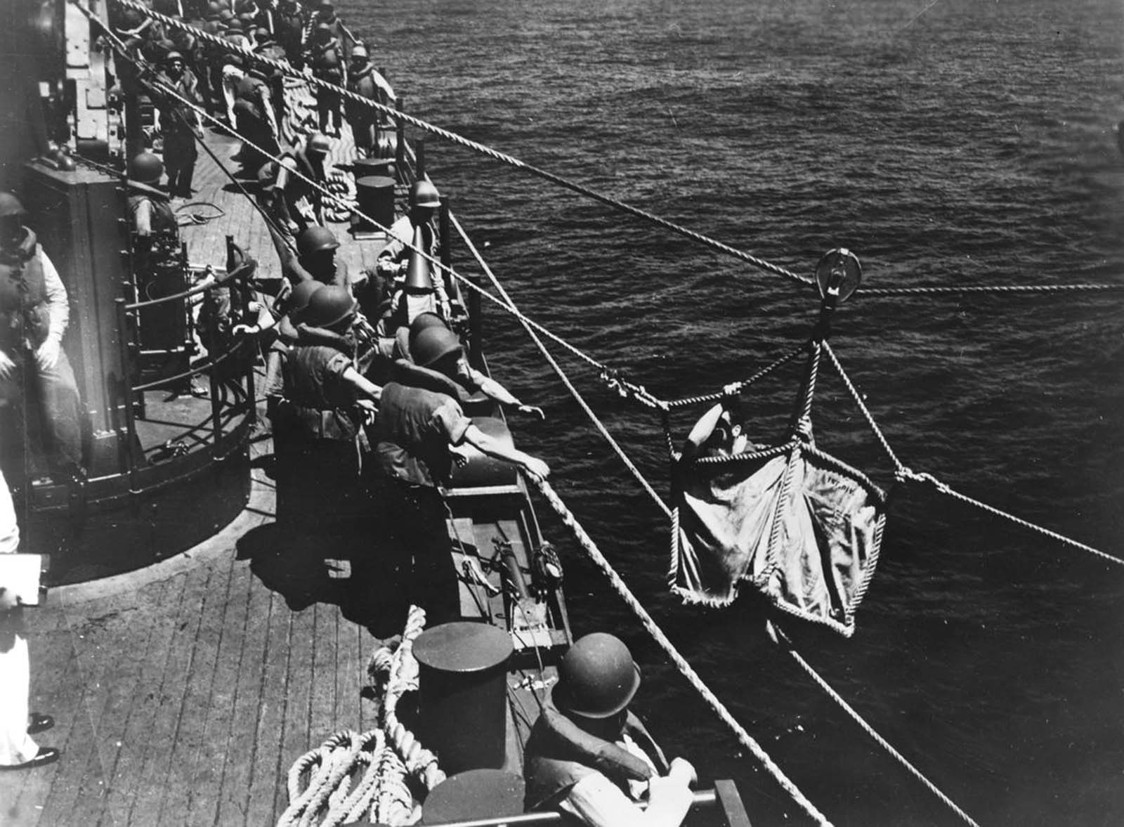 A U.S. seaman, wounded during the Battle of Midway, is transferred from one warship to another at sea in June of 1942.