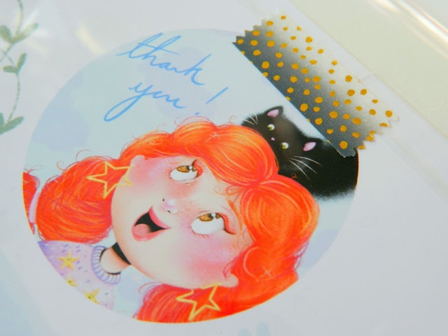 a photo of artwork showing a girl with ginger hair, a happy facial expression and golden star earrings. She had a black cat on her head and next to her, it says thankyou!