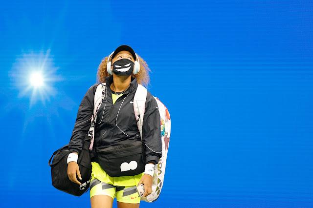 A tenista Naomi Osaka entra em quadra para a disputa de sua primeira partida no US Open 2021. Ela está de máscara, cobrindo corretamente a boca e o nariz. Ela segura seu celular, bolsa e raqueteira, com os equipamentos.