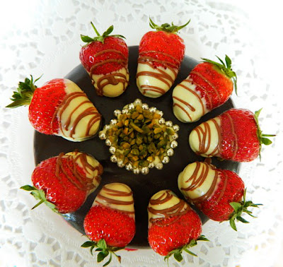 Strawberries smothered in chocolate on top of a cake