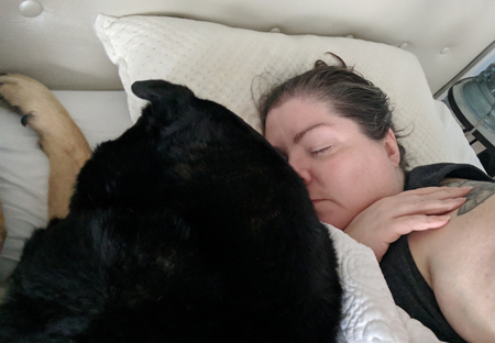 image of me lying in bed with my hair pulled back, falling asleep, with Zelda the Black and Tan Mutt lying beside me