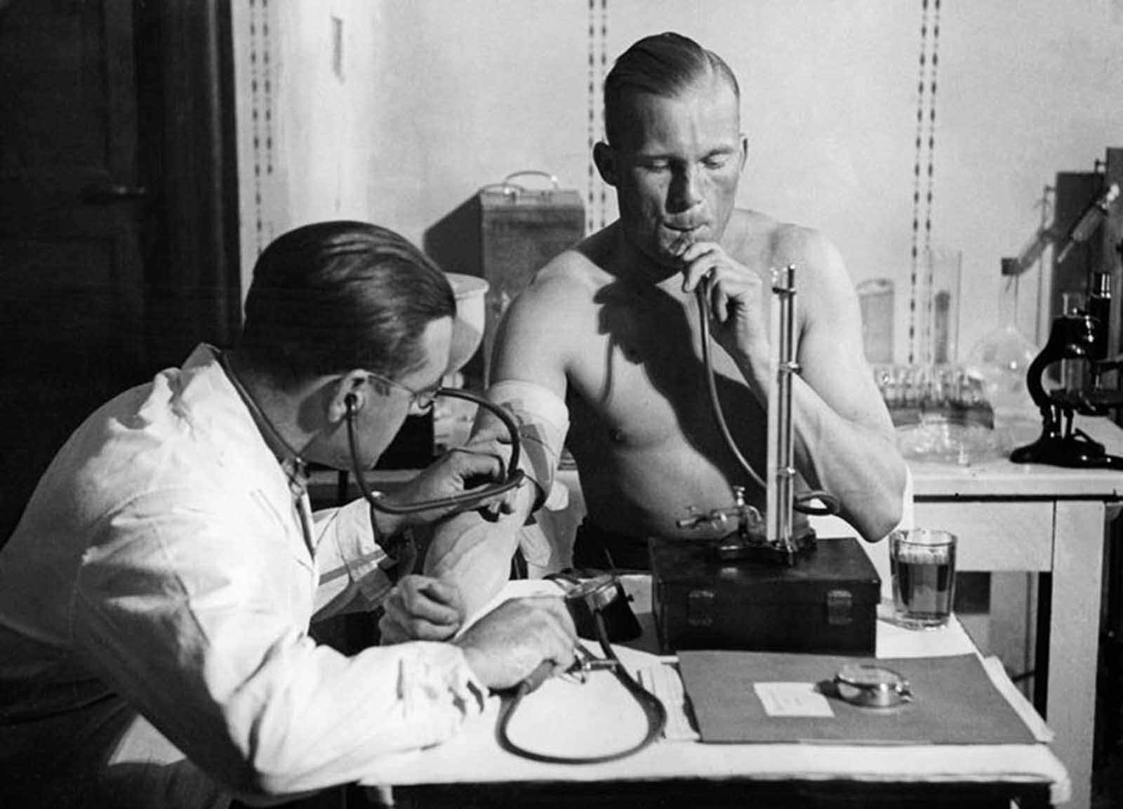 Lieutenant Radtke presses air into his lungs in a constant height with a mercury column, while the doctor checks his blood pressure, circa 1932.