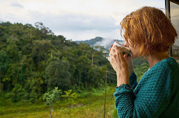 A women looking out in to the beautiful countryside while sipping from a mug