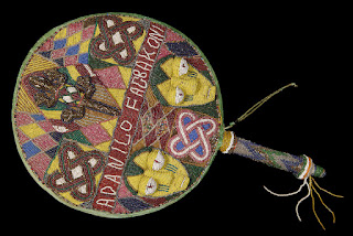 Photo of round fan covered in brightly coloured beads in a pattern featuring two human faces