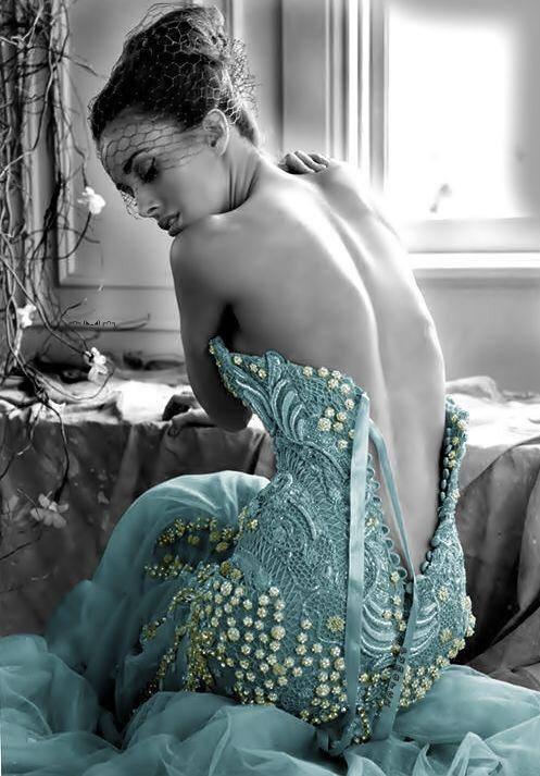 Uma jovem vestindo traje fino, sentada de costas com o zíper entreaberto, com ar de desolação e saudade.