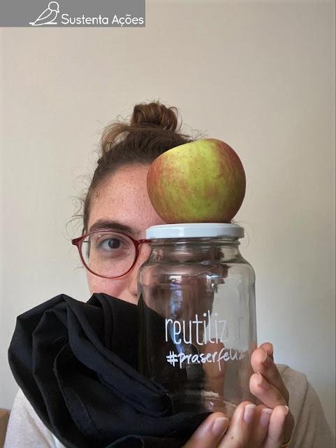 Letícia segurando um pote de vidro, uma maçã e uma sacola ecológica.