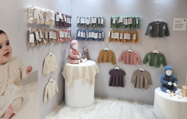 Image shows skeins of yarn hung up on two sides of a right angle wall, along with various coloured baby garments knitted in the yarn