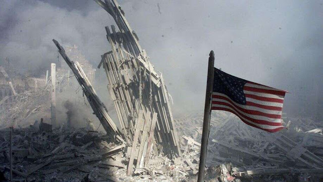 An American flag flies near the destroyed World Trade Center in New York City on Sept. 11, 2001, hours after the collapse of the towers. (REUTERS/Peter Morgan)
