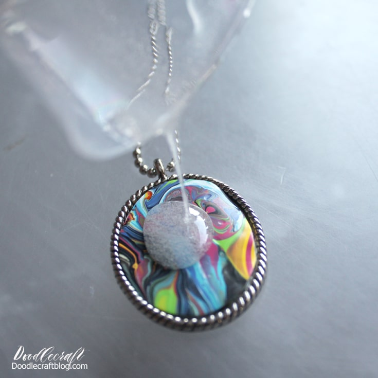 Supplies needed to make an acrylic paint poured dried skin pendant necklace with jewelry resin and silver plated bezel diy.