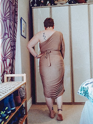 Sarah is stood with her back to the camera she is wearing a beige one shouldered dress