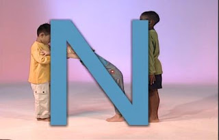 Three children form the letter N with their bodies. Sesame Street All Star Alphabet
