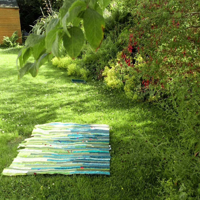 green quilt top made from strips, on the grass in a very green garden