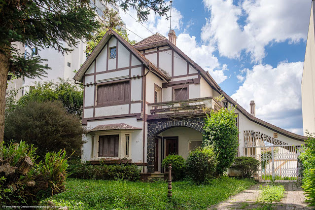 Casa com falso enxaimel, bay-window, varanda de entrada decorada com pedras, sacada, telhado bem inclinado