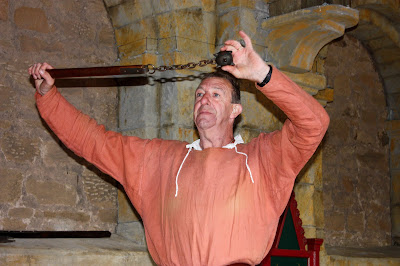 Photo of a man in medieval clothes holding up a flail... a stick with a chain and spiky metal ball on the end.