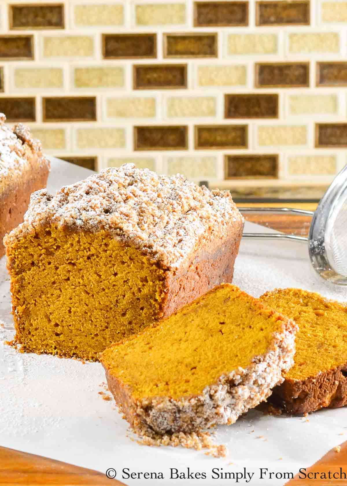 Sliced Pumpkin Bread with Streusel Topping lightly dusted with powdered sugar.