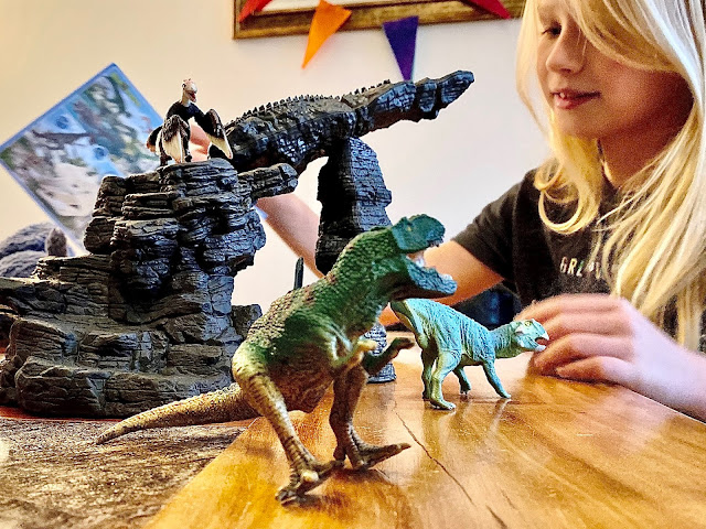A girl playing with the Schleich Dinosaur sets to review them. The cave is set up as a catapult