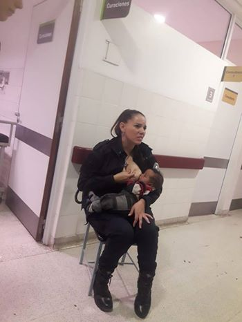 A police officer breastfeeds a malnourished baby while on duty