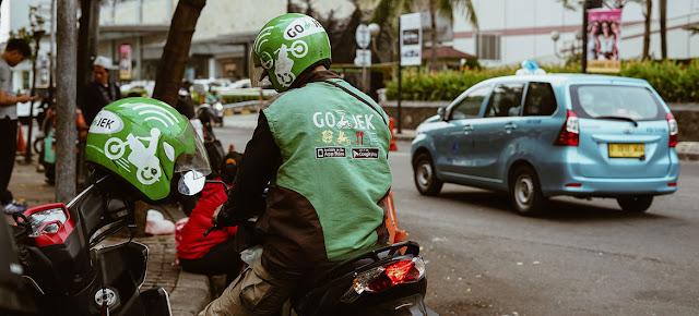 Un motociclista de una empresa indonesia de transporte espera a un pasajero. Unsplash/Afif Kusuma