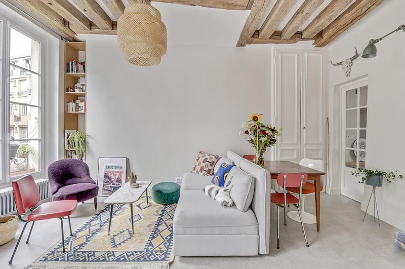 Salón con mobiliario a medida en el fondo y vigas decorativas.