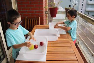 Duas crianças concentradas no seu desafio de empilhar maçãs