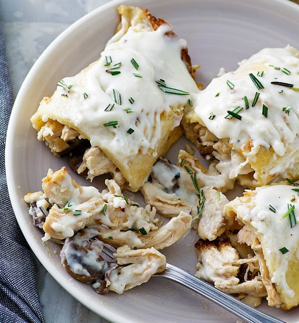 forkful of creamy lemon bechamel covered chicken and mushroom stuffed crepes