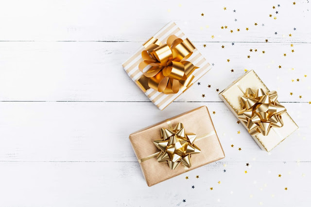 Christmas gifts wrapped with white and gold paper and ribbons