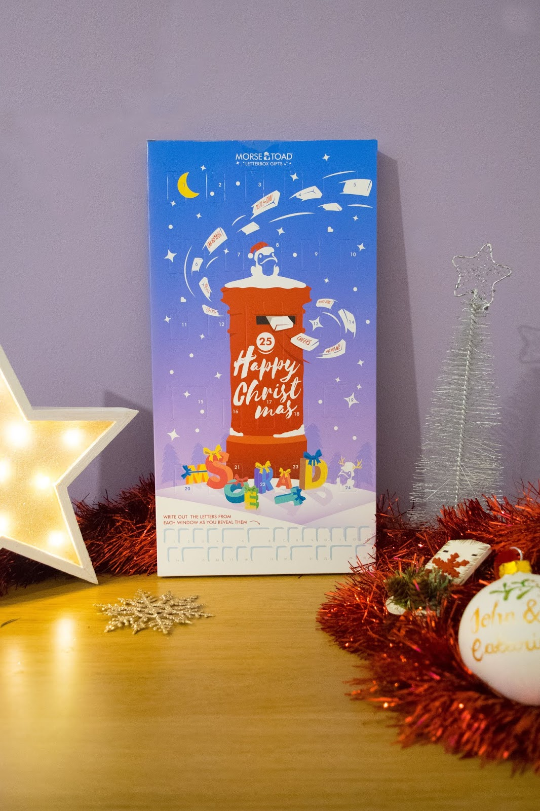 An advent calendar with a blue background and a red postbox covered in snow on the front. There is a frog with a Christmas hat on top of the postbox.