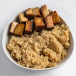 Square image of a bowl of quinoa with tofu