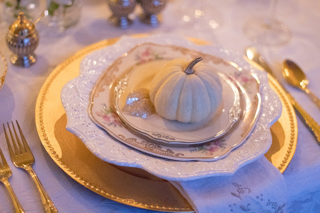 A fancy table setting for Thanksgiving, with a pumpkin on the plate