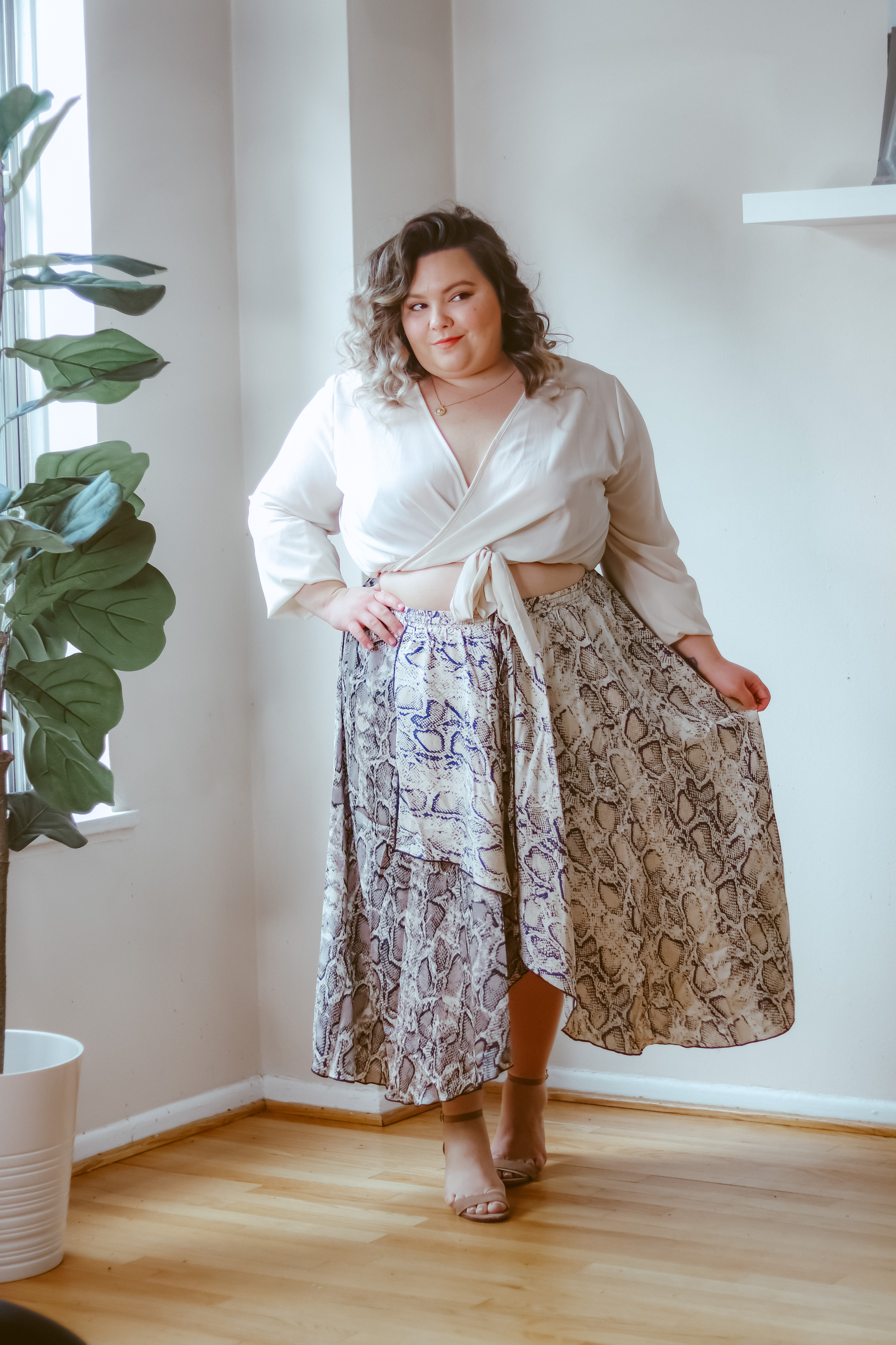 Chicago Plus Size Petite Fashion Blogger, influencer, YouTuber, and model Natalie Craig, of Natalie in the City, styles a snakeskin midi skirt.
