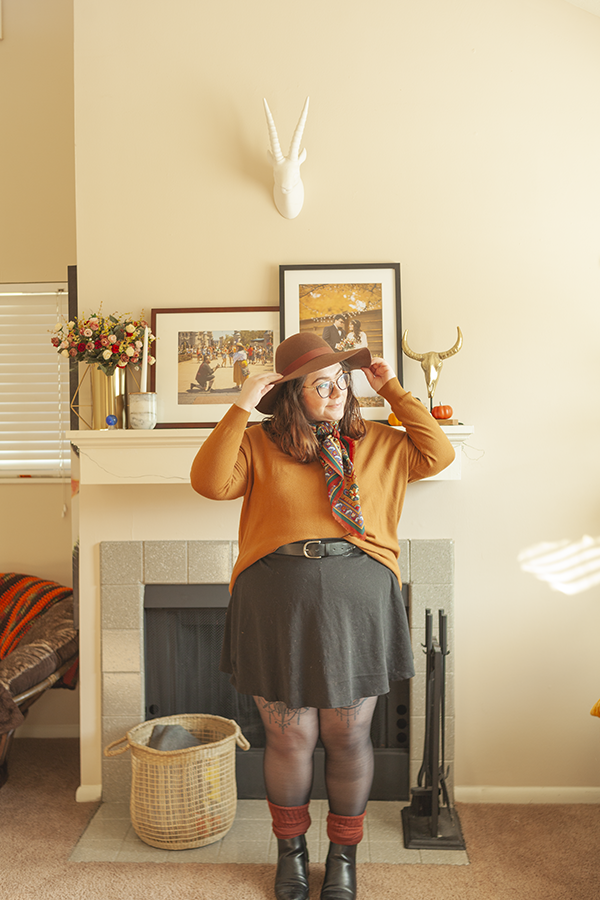 An outfit consisting of brown floppy hat, a yellow brown sweater tucked into a black skater skirt, with a rust red neck scarf, sheer tights, rust high socks that are scrunched down and black Chelsea boots.