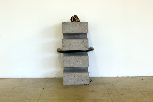 a sculpture on the floor, reaching knee-height, made of  bronze, concrete and steel. Description in text.