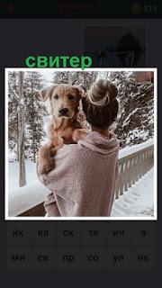 женщина на балконе в свитере и с собакой на руках в зимнее время