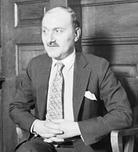 A balding, middle-aged white man with a mustache, clad in a suit and tie, sitting on a chair in front of a paneled wall