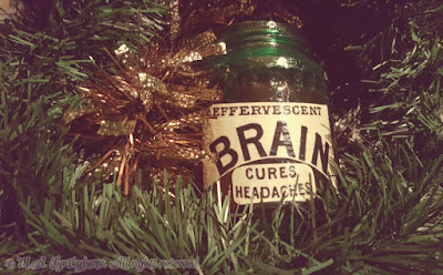 Photo of a glass jar surrounded by lush green and gold vines and labelled Effervescent Brain, Cures Headaches in a classic font