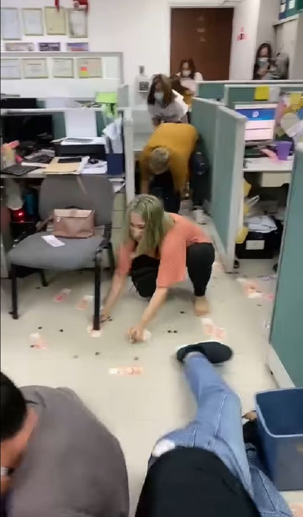 Workers scramble to pick money from floor in office game