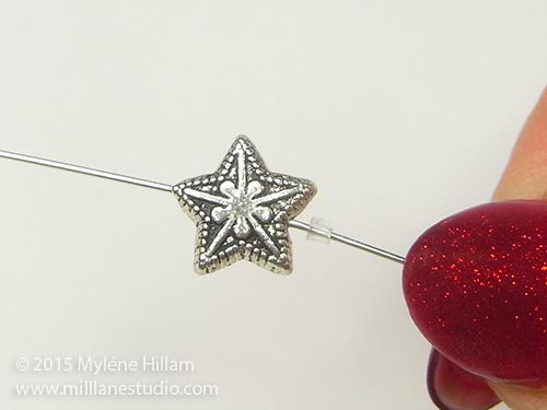String the star bead onto the eye pin.