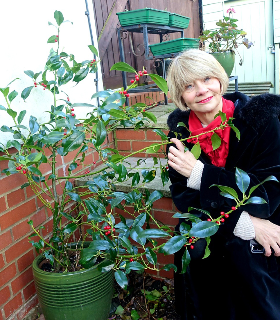 Close=-up with holly: over 50s blogger Gail Hanlon from Is This Mutton in black velvet coat and red accessories