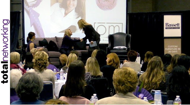 Total Networking Co-emcee Jen Mueller introduces panelist Shari Storm and Anne-Marie Faiola on stage in Seattle.