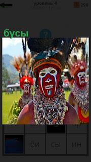 Мужчина абориген с разрисованным лицом и одеты бусы на шею