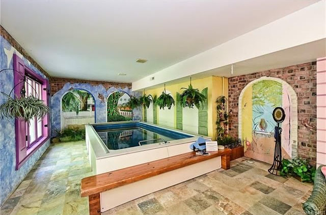A partially in-ground Endless Pools swimming machine in a Mediterranean-themed sunroom